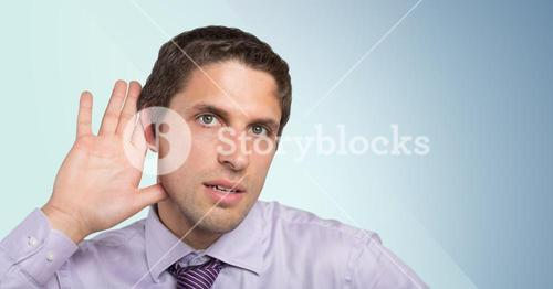 Man in lavender shirt with hand at ear against blue background