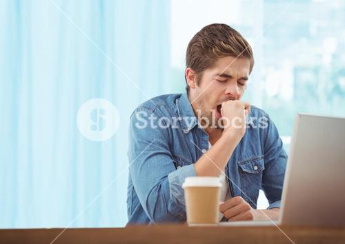 Man with laptop and coffee against blurry blue window