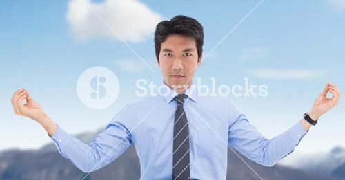Businessman Meditating against blue sky mountain