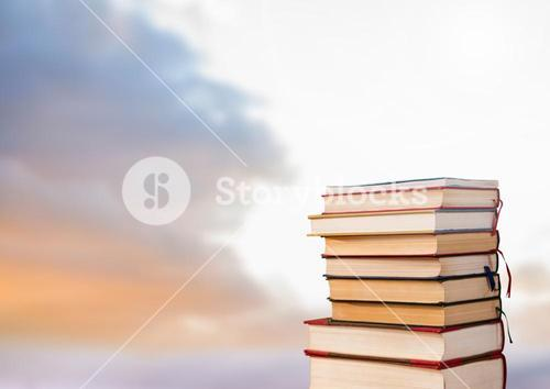Books stacked by cloudy sky