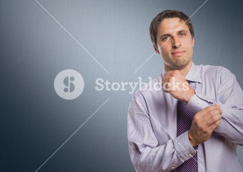 Man in lavender shirt holding arm against navy background