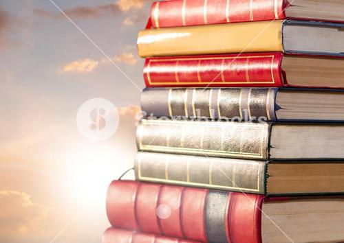 Books stacked by sun clouds