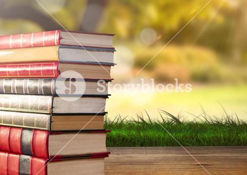 Books stacked by greenery nature