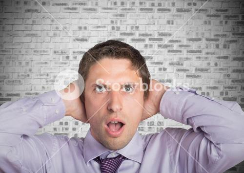 Man in lavendar shirt with hands on head against white brick wall