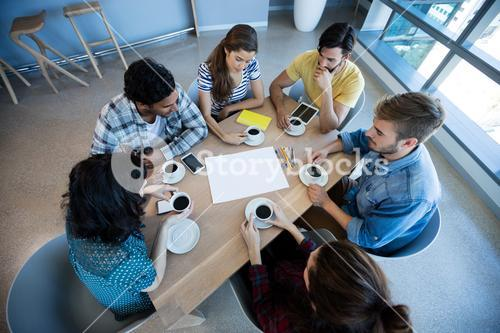 Creative business team having meeting over coffee in meeting room