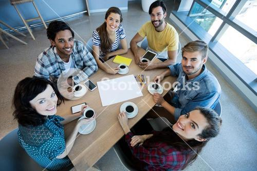 Creative business team having meeting over coffee in meeting room in office