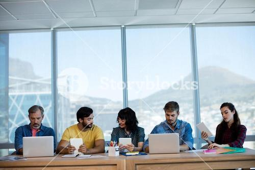 Creative business team sitting in a row and working together on table