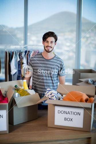 Smiling man standing with donation box in office