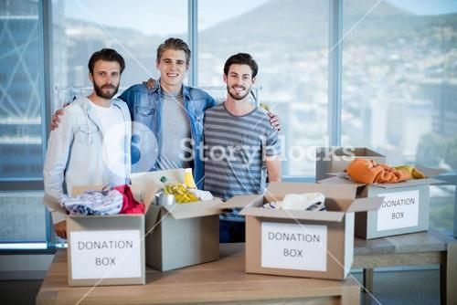 Smiling creative business team standing with donation box in office