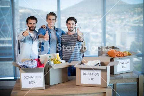 Creative business team standing near donation box and showing thumbs up
