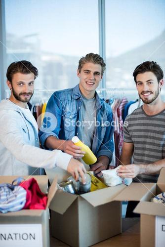 Creative business team sorting clothes in donation box