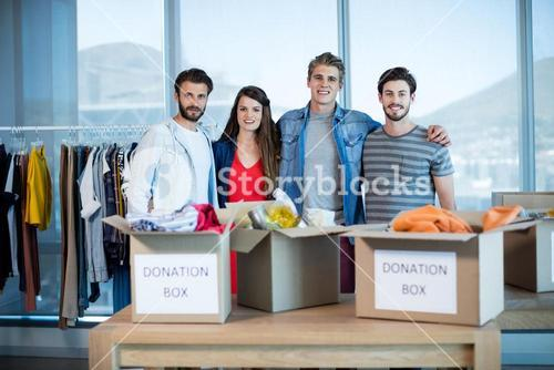 Smiling creative business team standing together with donation box