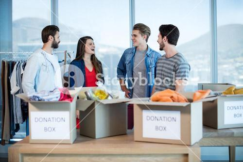 Creative business team talking near the donation box in office