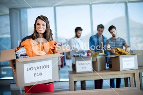 Smiling woman holding a donation box in office