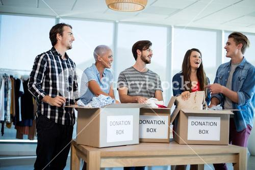 Happy creative business team sorting clothes in donation box