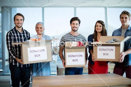 Creative business team holding donation box in office