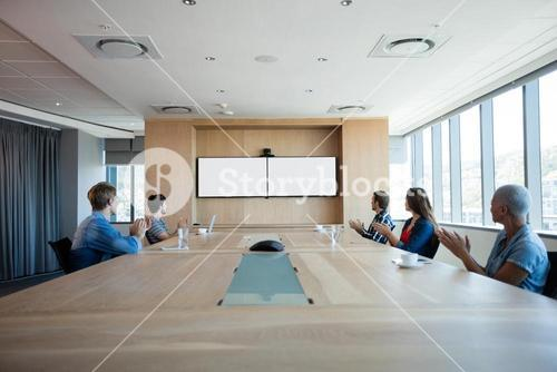 Creative business team applauding while attending a video call