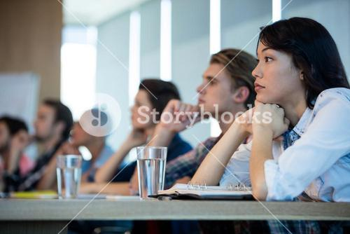 Creative business team listening at meeting in conference room