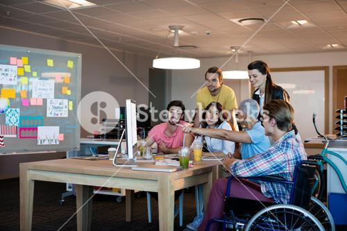Creative business team discussing while working together on desktop pc