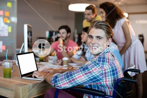 Smiling man using laptop while working with his team in office