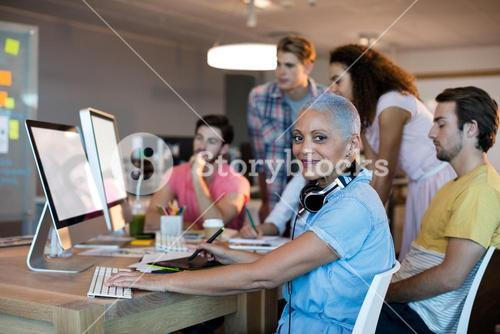 Woman working on desktop pc with her team