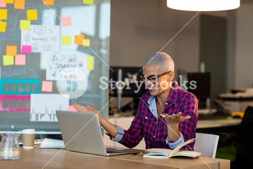 Overjoyed creative businesswoman sitting on desk