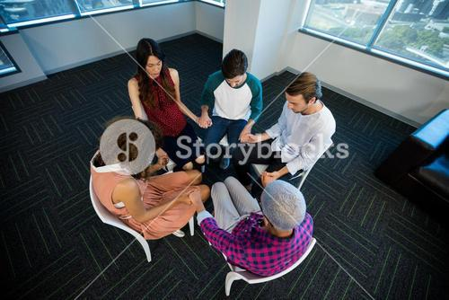 Creative business team holding each others hand at office