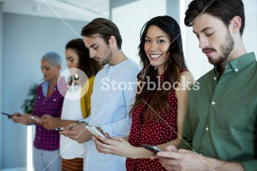 Smiling woman using mobile phone with their colleagues in office