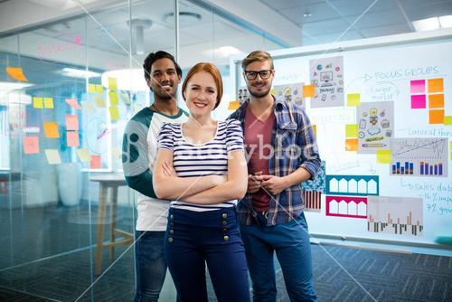 Smiling creative business team standing against sticky notes in office