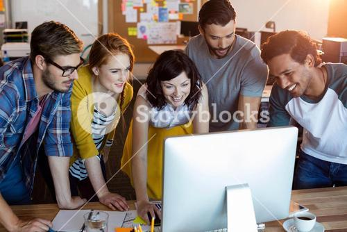 Creative business team working together on desktop pc in office