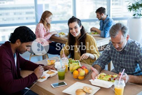 Creative business team having meal in office