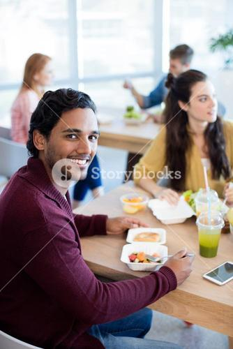 Smiling man having meal at office