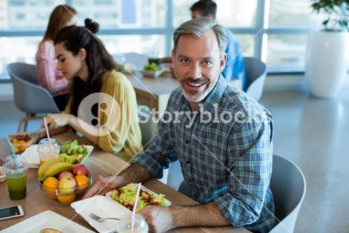 Smiling man having meal with his colleagues