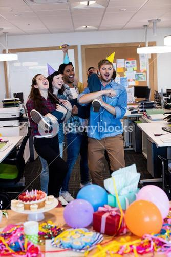 Creative business team celebrating and lifting a college