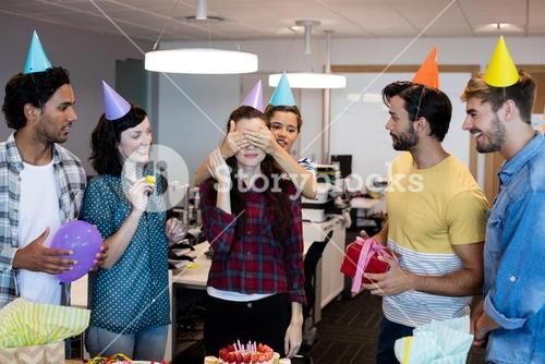 Creative business team giving a surprise to their college on her birthday