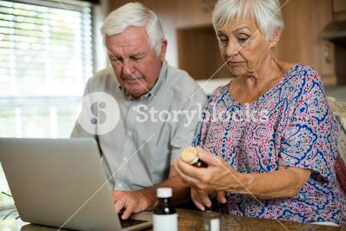 Senior couple using laptop and holding pill bottle in kitchen