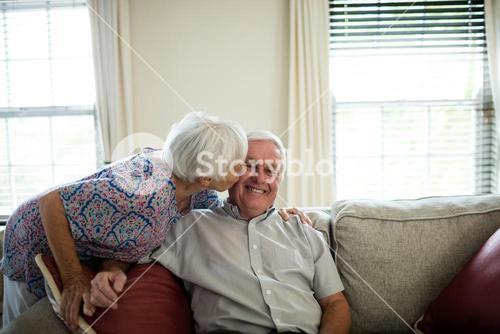 Senior woman kissing senior man in living room