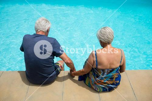Senior couple relaxing at poolside
