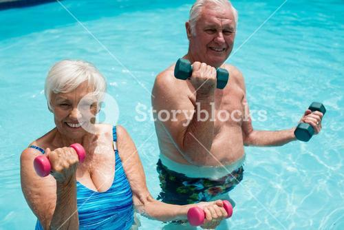 Senior couple exercising with dumbbells in the pool