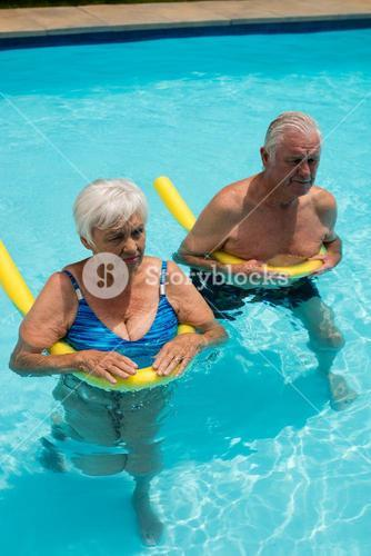 Senior couple swimming in the pool with inflatable tubes
