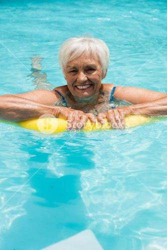 Senior woman swimming with inflatable tube