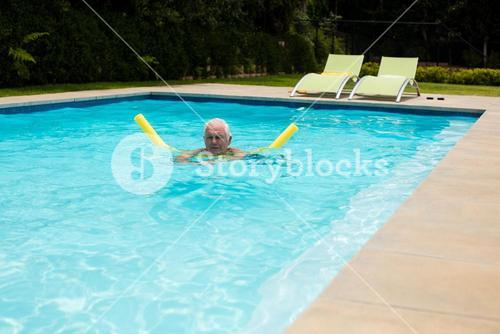 Senior man swimming with inflatable tube