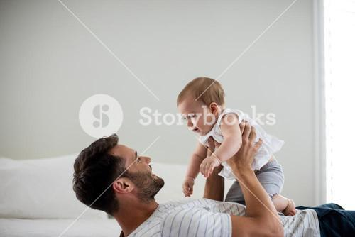 Father playing with his baby in bedroom