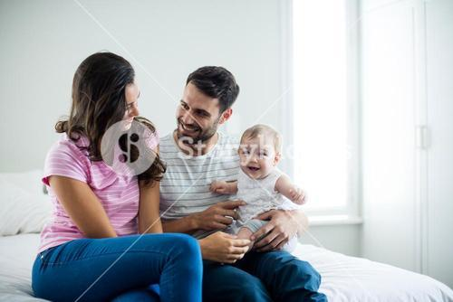 Couple with playing with baby girl in bedroom