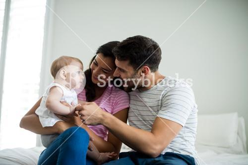 Couple playing with their baby girl in bedroom