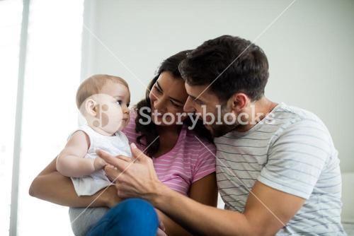 Parents playing with their baby girl in bedroom