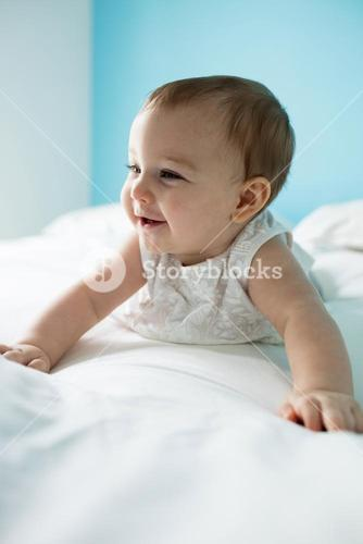 Cute smiling baby girl on bed