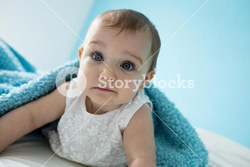 Cute baby girl lying on bed