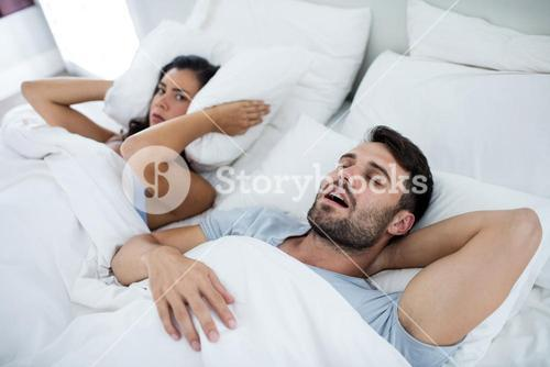Woman getting disturbed with man snoring on bed
