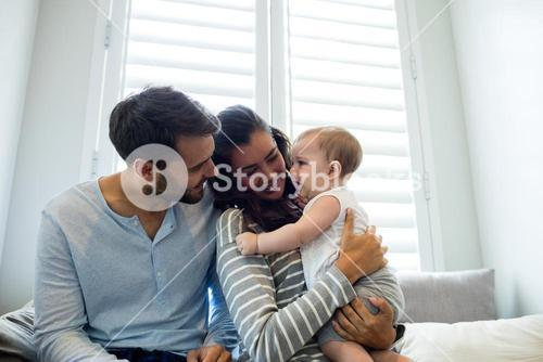 Couple holding their baby girl in bedroom